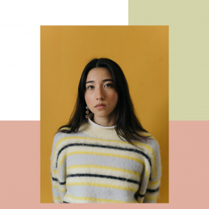 artist maya man looking at the camera and standing against a yellow backdrop. she is wearing a beige sweater with yellow and green stripes