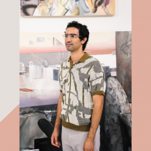 artist Leo Castenada standing in his studio wearing a gray an white patterned polo and gray pants.