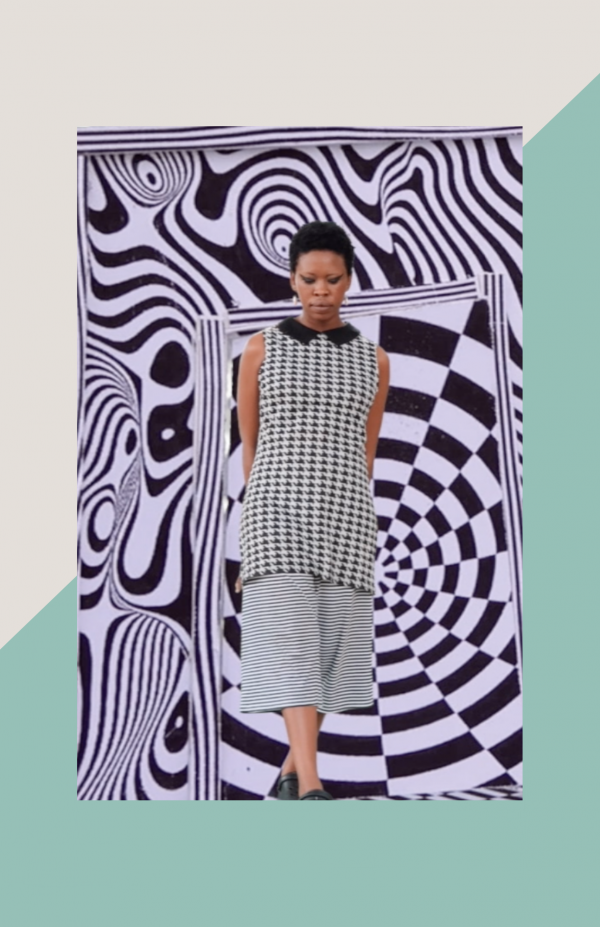 Natalie Paneng, a black woman with short hair, wearing a black and white small pattern top and pants against a black and white eye illusion background