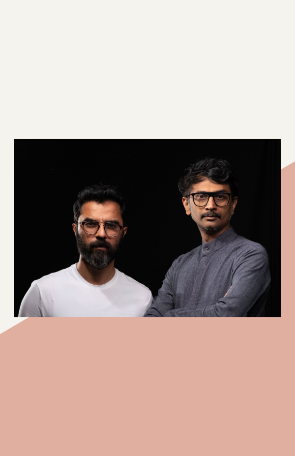 artists thukral and tagra standing next to each other against a black backdrop. one is wearing a white t-shirt and has a beard and glasses, the other wears a gray tunic and has glasses and a mustache